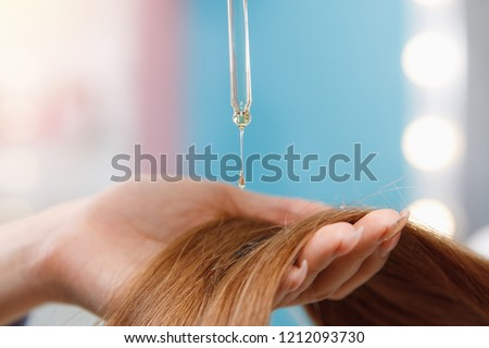 Close-up drop of oil restore and recovery hair is applied to head bulbs. Concept hairdresser spa salon.
