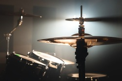 Close-up Drum set in a dark room against the backdrop of the spotlight. Atmospheric background symbol of playing rock or jazz drums. Copper plates on a cold background