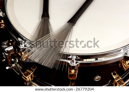 close up drum with drumsticks on black background
