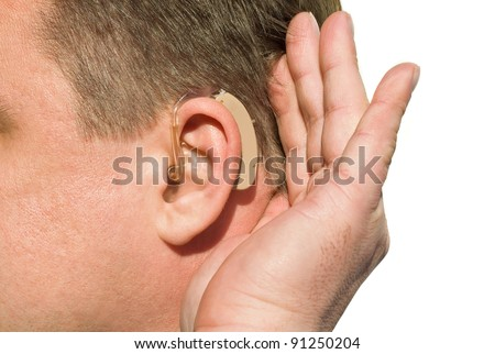 Close up ear of a man wearing hearing aid and listening for a quiet sound.
