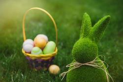 Close up Easter bunny rabbit statuette and basket with easter eggs on the green grass lawn background. Easter egg hunt in the garden. Selective focus, copy space.