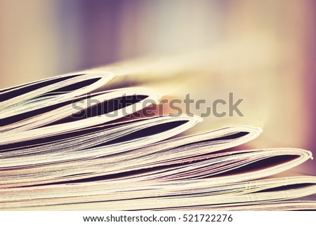 Close up edge of colorful magazine stacking with  blurry bookshelf background for publication and publishing concept , extremely shallow DOF  with vintage retro color tone