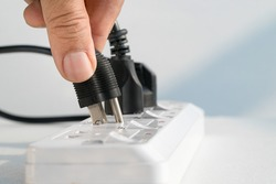Close up Elderly hand plugging into electrical outlet