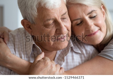 Close up elderly man woman embracing 70s husband and mature wife closed eyes feels calm peaceful moment of tenderness and love, middle aged daughter cuddle old father multi generational family concept