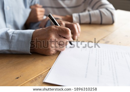 Close up elderly senior family couple signing contract with real estate agent purchasing accommodation, making agreement with financial advisor or putting signature on paper medical insurance. Foto stock ©