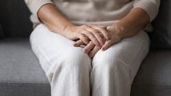 Close up elderly senior woman sitting on sofa, holding folded hands on lap, feeling lonely at home. Middle aged mature lady suffering from depression, recollecting memories alone in living room.