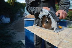 Close up electric saw to sawing wood board, solf focus. Plywood Cut by Circular Saw. Construction Worker and the Woodworking