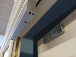close-up electromagnetic lock mounted on a wooden door to restrict access to the room, access via access card