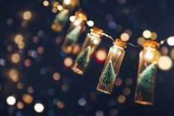 Close-up, Elegant Christmas tree in glass jar with bokeh lights background, copy space. Christmas and new year concept.