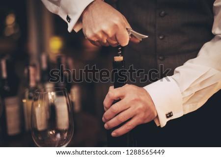 Close up. Elegant sommelier uncorking bottle of wine in restaurant. Wine tasting. Sommelier tasting wine in restaurant. Stock photo ©