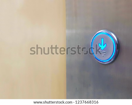 Close up Elevator circle button down direction with blue light on wall. Copy space #1237668316