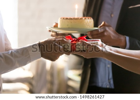 Close up employees congratulating colleague with birthday or promotion, giving gift box with bow and cake with candle, party in office, friendly workers making surprise, corporate celebration concept