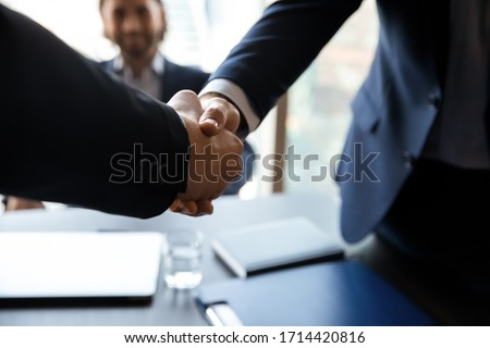 Close up employer shaking successful candidate hand at meeting, greeting, welcome or respect, congratulating with getting job after interview, business partners handshaking, making good deal