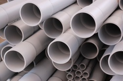 Close up ends of PVC conduit pipes on a stack. Nice gray texture background for construction site