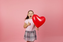 close-up enthusiastic, ecstatic, rapturous girl in pink dress holds a red balloon in the shape of a heart and gives a thumbs up isolated on a pink background.