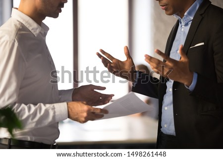 Close up executive manager dissatisfied by African American employee work results, holding financial report with stats, colleagues arguing, discussing business failure, partners disputing at work