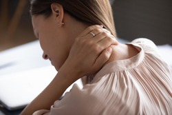 Close up exhausted woman touching massaging tensed neck muscles, feeling unwell after long hours sedentary work, uncomfortable chair, incorrect posture, young female suffering from pain, ache