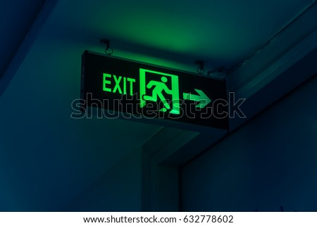 Close-up Exit neon or led sign in corridor point way out of resident apartment building in Hanoi, Vietnam. Lighted wall mounted shining signboard show escape of emergency, urgency, firer. Vintage tone