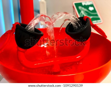Close up Eye wash station and push on button for flowing the water washing eyes, when touch with Acid or toxic chemical, safety first protection equipment in chemistry laboratory. Selective focus.