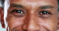 Close-up face african descent closing and opening eyes, smiling reaction