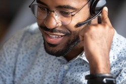 Close up face african man telesales worker working wear headset contacting customers to inform them about service, answer questions about products. Call center operator agent, clients support concept
