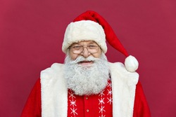 Close up face headshot portrait of funny happy old bearded Santa Claus face wearing hat, glasses, looking at camera, laughing, standing on Merry Christmas, Happy New Year isolated on red background.