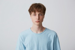 Close up face of a young man without emotions. Beautiful emotionless guy in a blue t-shirt looking to the camera, isolated over white background