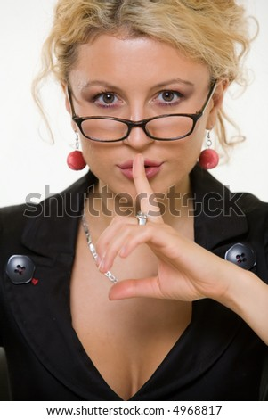 Close up face of an attractive blond woman dressed in business attire wearing dark framed eyeglasses holding finger to lips to gesture for silence