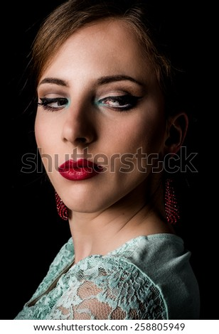 Close up Face of an Elegant Young Woman with Make up Staring to the Bottom Right of the Frame on a Black Background.