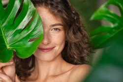 Close up face of beautiful young woman covering her face by green monstera leaf while looking at camera. Portrait of beauty woman with natural makeup and freckles standing behind big green leaves.