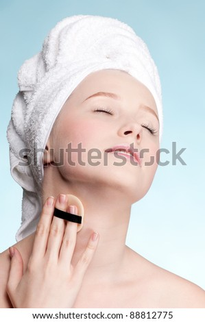 Close-up face of beauty young woman applying sponge - stock photo
