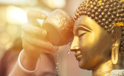 Close up Face of Buddha statue with Hand of sprinkle water onto a Buddha image. Buddhism ceremony, Believe of Buddhist concept. Make merit and worship concept. Songkran the most famous of Thailand.