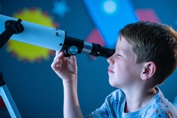 Close up face of curious kid child using telescope to explore moon surface. Little boy stargazing at night with a telescope to see galaxy from his room decorated bedroom with rocket in background.