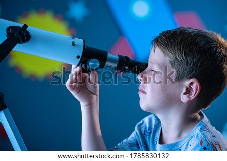 Close up face of curious kid child using telescope to explore moon surface. Little boy stargazing at night with a telescope to see galaxy from his room decorated bedroom with rocket in background. Stock photo ©