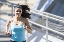 close up face of young beautiful and athletic sport woman running and jogging in urban training workout crossing modern metal city bridge in female runner body care and healthy lifestyle concept