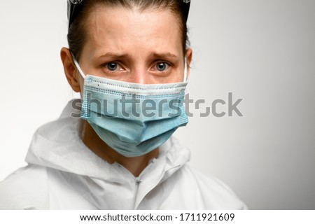 Close-up. Face of young girl in blue medical mask with sad expression on grey background.