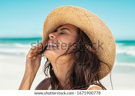 Close up face of young stylish woman wearing straw hat at beach. Happy tanned latin woman laughing during summer holiday. Beautiful fashionable girl relaxing at beach while holding large brim for wind