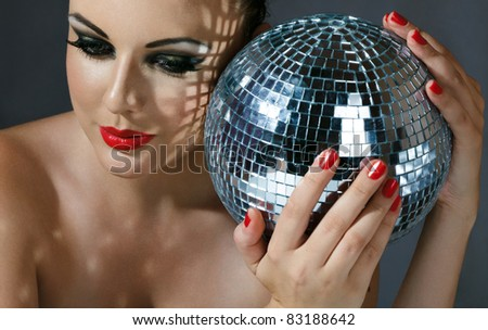 Close-up face of young woman with fashionable make-up and disco ball in hands