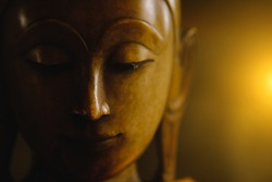 close up face on buddha head statue with lighting effect.  Selective focus face buddha statue.