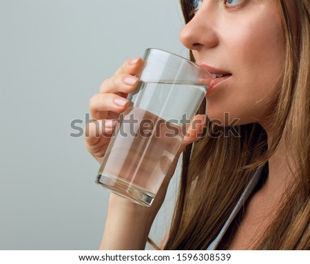 Close up face portrait drinking water from glass. isolated female portrait.