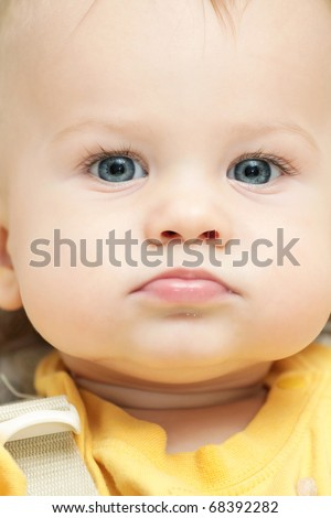 Close up face portrait of a baby boy, strapped in a chair or car seat