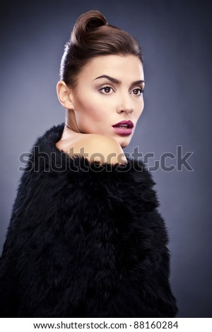 Close-up face portrait of stylish&fashionable pretty woman in fur against grey background.