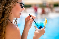 close up face profile portrait of young beautiful caucasian woman with long brown hair wearing sunglasses drinking blue cocktail though a straw over outdoor poolside area blurred bckground.