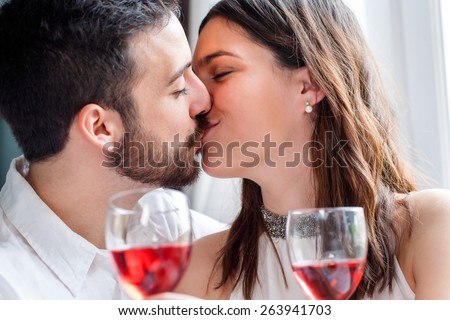 Close up face shot of couple kissing at romantic dinner. Out of focus wine glasses in foreground.