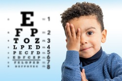 Close up face shot of little Afro American boy testing vision. Kid with closing on eye with hand. Vision chart with block letters and focus point in background.