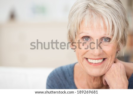 Close up facial portrait of a beautiful senior woman looking at the camera with a warm friendly smile and attentive expression