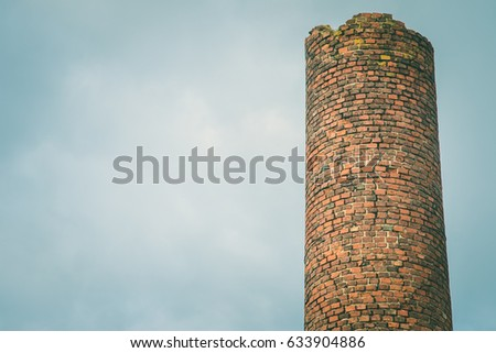 close-up factory brick chimney. The smoke from the pipe cogeneration plant. Steam escaping from a trumpet on the sky background in the sunlight. Ambient air pollution industrial emissions #633904886