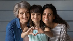 Close up family portrait of happy three generations of Hispanic women pose together show love heart hand gesture. Smiling little Latino girl child with young mother and senior grandmother feel united.