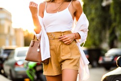 Close up fashion details of stylish woman posing the street wearing trendy casual fashionable outfit, beige short, white tip and caramel luxury leather bag, street style, vacation mood.