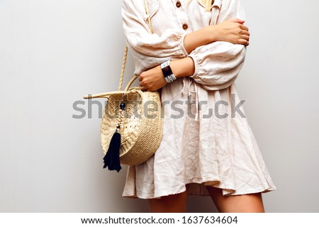 Close up fashion details of woman wearing linen boho dress, trendy straw hat and accessories, posing at creamy white background.